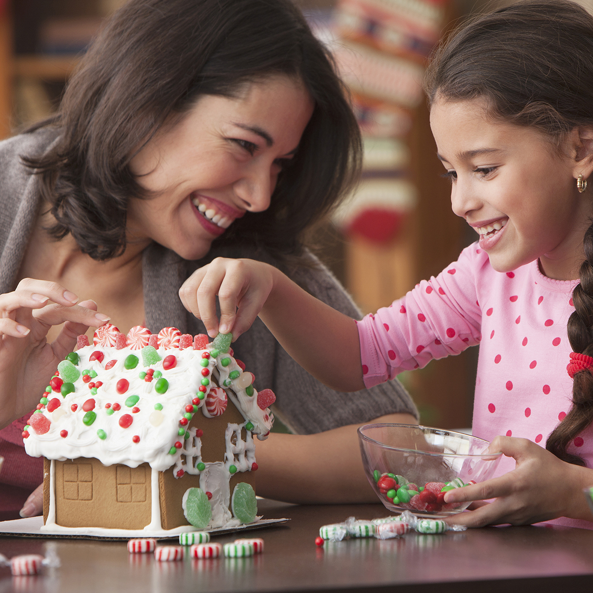 Mother and daughter decorating gingerbread house